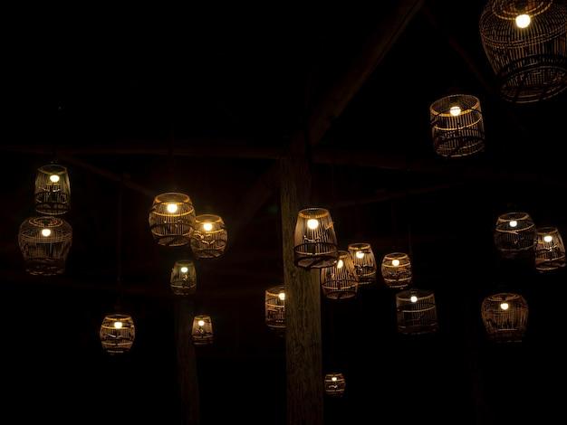 Schön von einer gruppe von deckengeflecht-bambusgewebelampe, die im dunkeln leuchtet viele hängende laternenbambus, beleuchtungsdekoration, asiatischer stil.