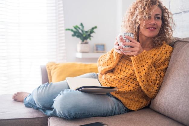 Schöne 40-jährige kaukasische dame setzt sich auf das sofa, trinkt tee und liest ein buch für die nachmittags indoor-freizeitaktivität zu hause