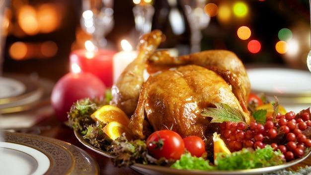 Schöne 4k-aufnahmen von leckerem gebackenem hühnchen auf reich verziertem goldenem teller gegen weihnachtsbeleuchtung und brennende feuerstelle. esstisch für die große familie an winterferien und feiern.