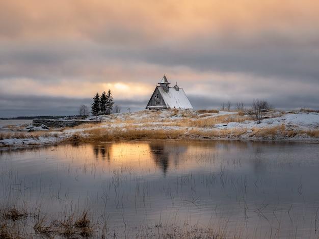 Schöne abendliche winterlandschaft mit einem kleinen authentischen holzhaus in der abenddämmerung auf einer klippe. russland.