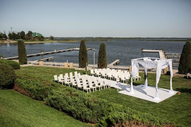 Schöne abgehende hochzeitseinrichtung. jüdisches hupa auf der romantischen hochzeitszeremonie, heiratend im freien auf der rasenwasseransicht