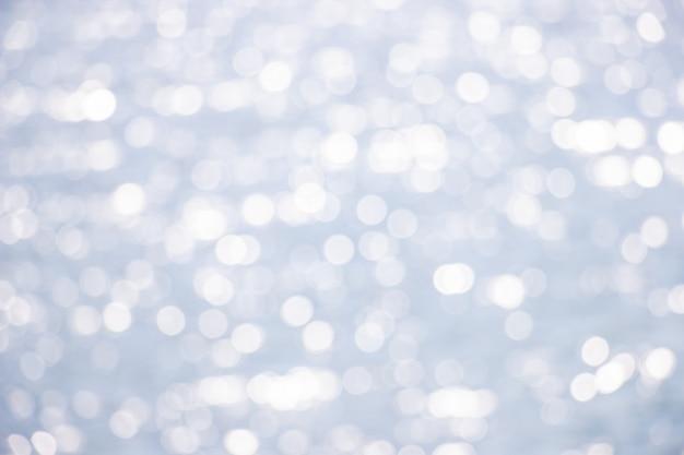 Schöne abstrakte hintergrund bokeh sonnenlichtreflexionen auf blauem flussoberflächenwasser.