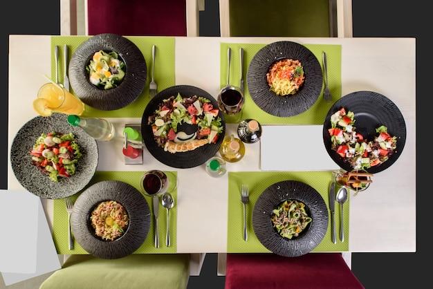 Schöne abwechslungsreiche restaurantgerichte auf dem tisch, draufsicht. salate, pasta pasta mit meeresfrüchten und getränken auf dem tisch. sitzordnung bei tisch.