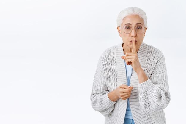 Schöne ältere dame hat wenig geheimnis und bittet niemanden, weihnachtsüberraschung für ehemann vorzubereiten. großmutter erzählt, bleib ruhig und zeige eine stille geste, drücke den zeigefinger auf die gefalteten lippen
