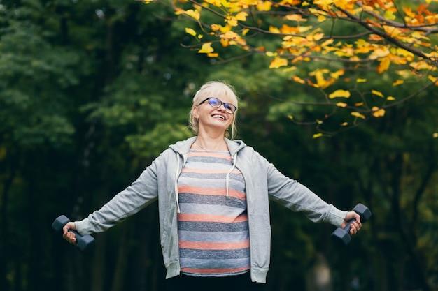 Schöne ältere frau auf einem spaziergang im park, führt übungen mit hanteln in ihren händen durch