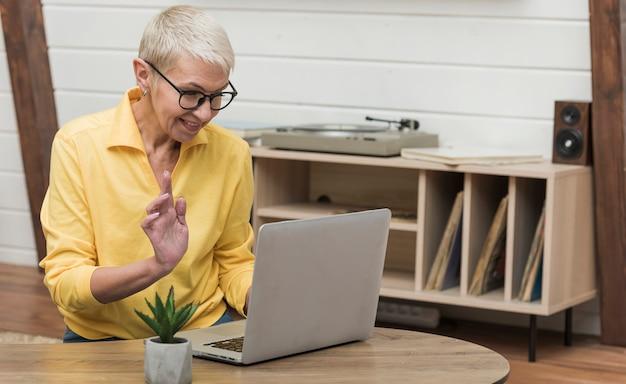 Schöne ältere frau, die durch das internet auf ihrem laptop schaut