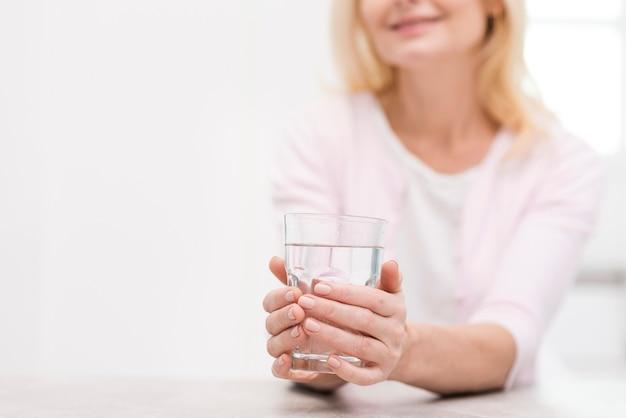 Schöne ältere frau, die ein glas wasser anhält