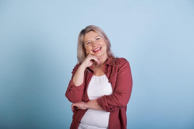 Schöne ältere frau, die ihr kinn berührt und auf blaue studiowand lächelt