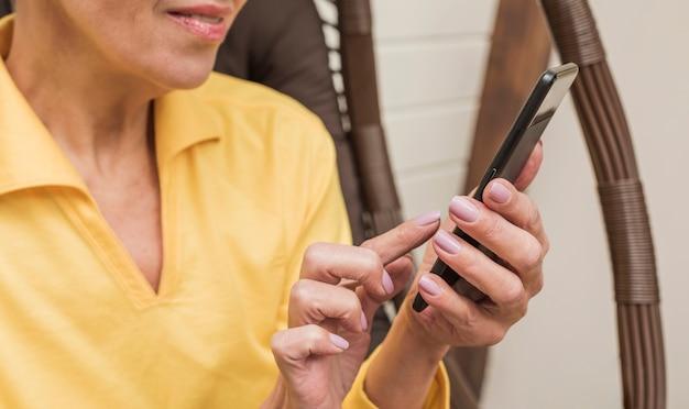 Schöne ältere frau, die ihre telefonnahaufnahme verwendet