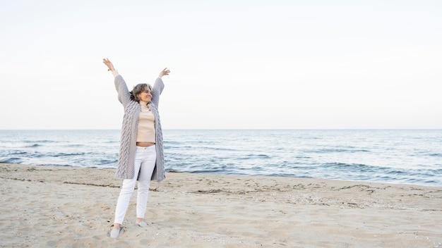 Schöne ältere frau, die ihre zeit am strand genießt