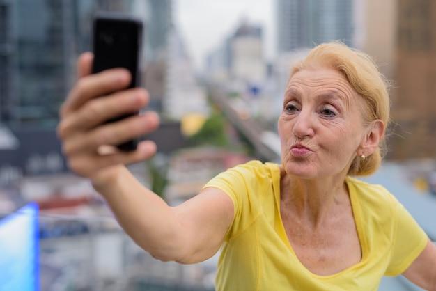 Schöne ältere frau, die selfie mit handy in der stadt nimmt