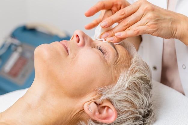 Schöne ältere frau, die spa-massage-behandlung im beauty-spa-salon bekommt. schönheitsbehandlung im gesicht.