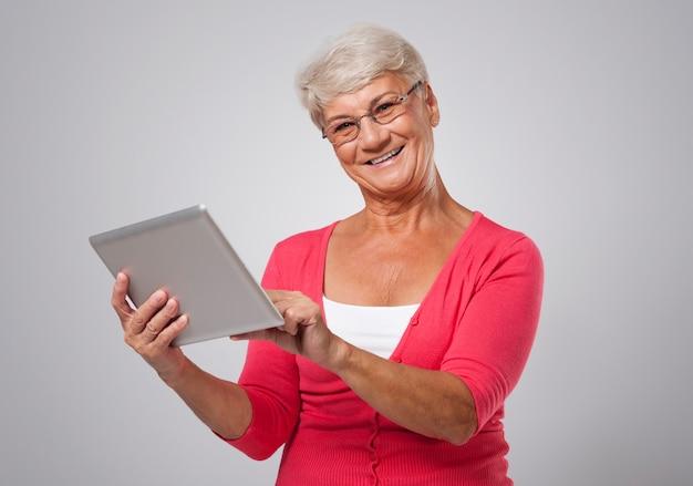 Schöne ältere frau, die zeitgenössisches digitales tablett verwendet