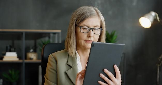 Schöne ältere frau in den gläsern, die auf computer im büro tippen und scrollen.