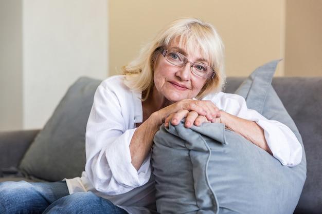 Schöne ältere frau in der brille, die sich auf ein kissen stützt
