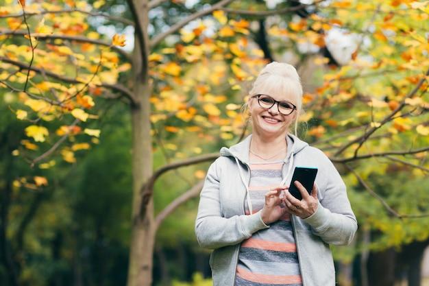 Schöne ältere frau in einem rucksack auf einem spaziergang im park, am telefon sprechend