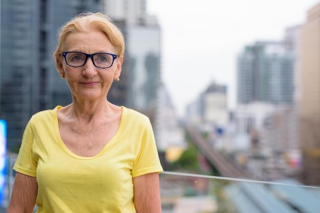 Schöne ältere frau mit blondem haar gegen ansicht der stadt