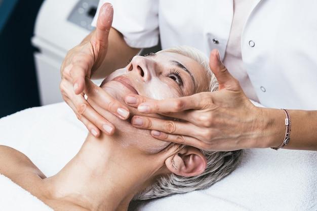 Schöne ältere frau mit chemischer peeling-schönheitsbehandlung. die erfahrene kosmetikerin trägt eine chemische lösung auf das gesicht der frau auf.