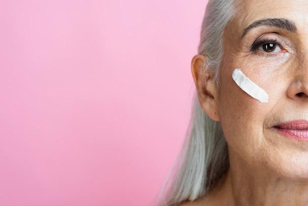 Schöne ältere frau mit hautpflegebehandlung
