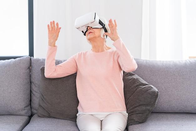 Schöne ältere frau mit vr-google zu hause reife frau, die mit der welt der virtuellen realität spielt Premium Fotos
