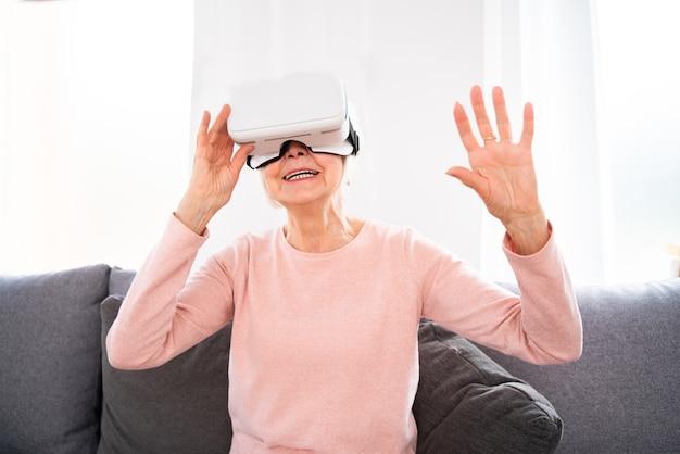 Schöne ältere frau mit vr-google zu hause reife frau, die mit der welt der virtuellen realität spielt