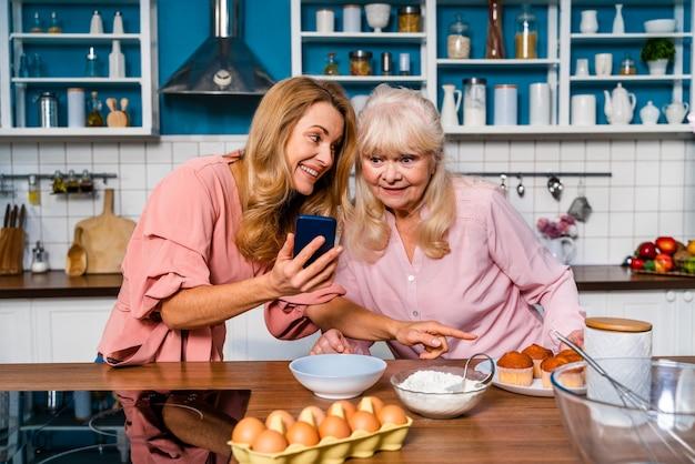 Schöne ältere frau und tochter, die in der küche großmutter backen, die desserts zu hause mit familie zubereitet und rezept im internet betrachtet