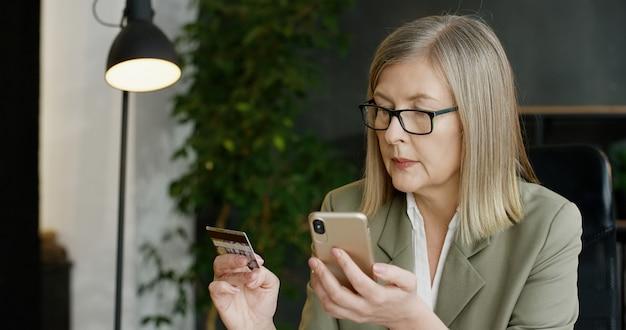Schöne ältere geschäftsfrau, die kreditkarte hält und online auf smartphone einkauft.