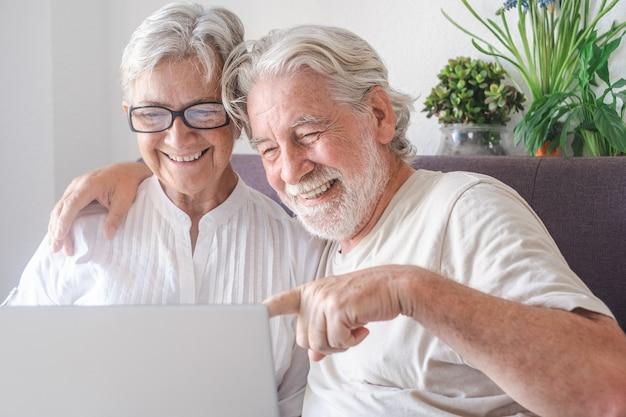 Schöne ältere paare, die das laptop-computerlachen verwenden. gelassene ältere menschen, die technologie und soziales genießen
