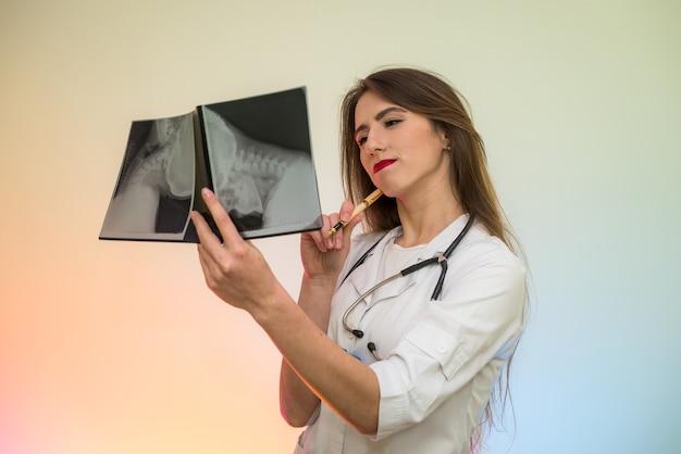 Schöne ärztin, die auf röntgen im krankenhaus zeigt. arzt stellt diagnose