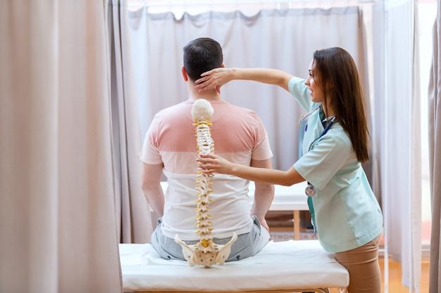 Schöne ärztin, die das wirbelsäulenmodell hält und die wirbelsäule des patienten untersucht.