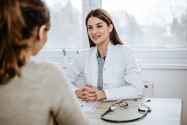 Schöne ärztin im weißen medizinischen mantel konsultiert ihren patienten.
