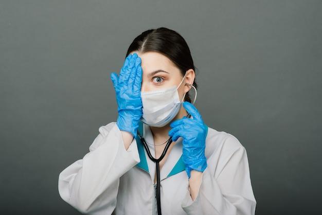 Schöne ärztin in der schutzmaske, die weg schaut und an etwas denkt.