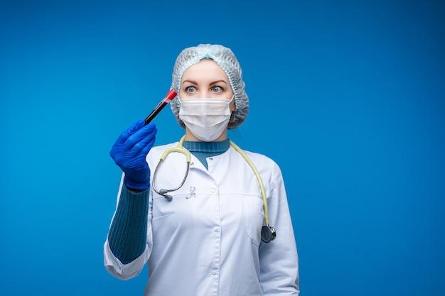 Schöne ärztin in weißer medizinischer kleidung, maske, phonendoskop und medizinischem hut betrachtet blut in vitro