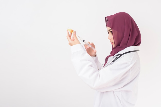 Schöne ärztin mit hijab hält impfstoff auf weißem hintergrund