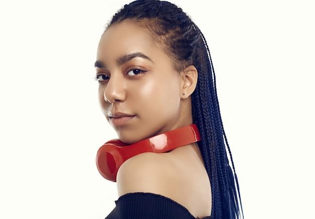 Schöne afrikanische brunettejugendliche mit hörender musik der dreadlocks