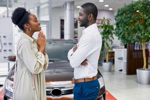 Schöne afrikanische dame bittet ihren mann, ein auto zu kaufen