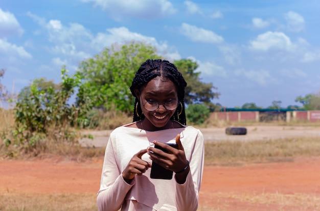 Schöne afrikanische dame, die aufgeregt ist über das, was sie auf ihrem handy gesehen hat