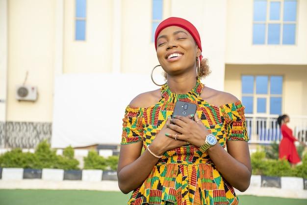 Schöne afrikanische dame, die ihr telefon an ihre brust hält, gefüllt mit freude