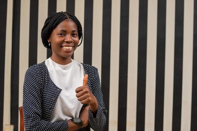 Schöne afrikanische dame, die sich aufgeregt fühlt, als sie daumen hoch tat