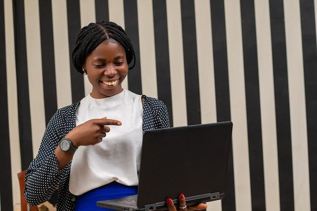 Schöne afrikanische dame, die sich überreizt fühlt, als sie auf ihren laptop zeigt