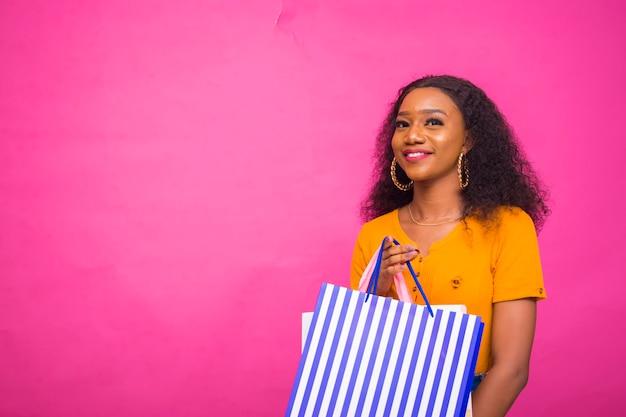 Schöne afrikanische dame isoliert über rosafarbenem hintergrund, die aufgeregt ist, während sie eine einkaufstasche hält.