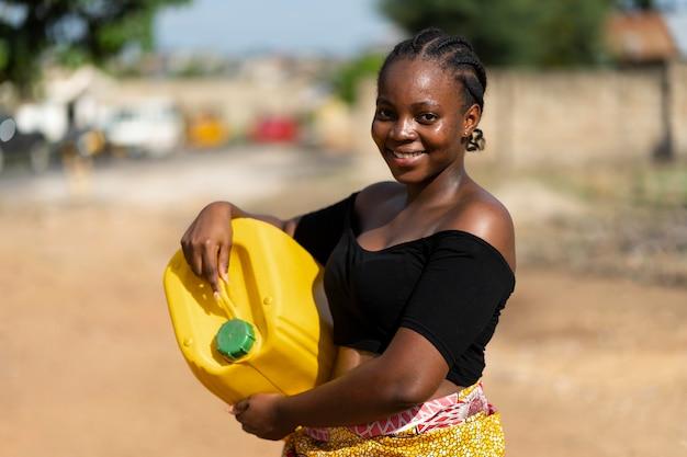 Schöne afrikanische frau, die einen gelben wasserempfänger hält