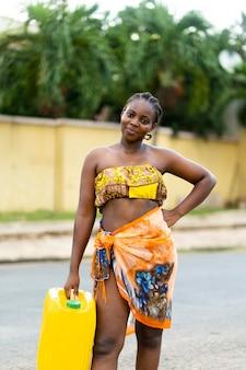 Schöne afrikanische frau, die einen wasserempfänger hält