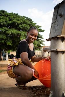 Schöne afrikanische frau, die etwas wasser in einen eimer gibt