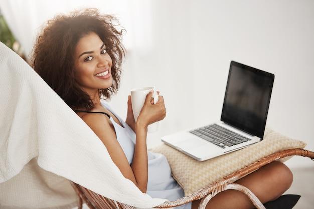 Schöne afrikanische frau in der nachtwäsche lächelnd, die tasse hält, die mit laptop im stuhl allein zu hause sitzt