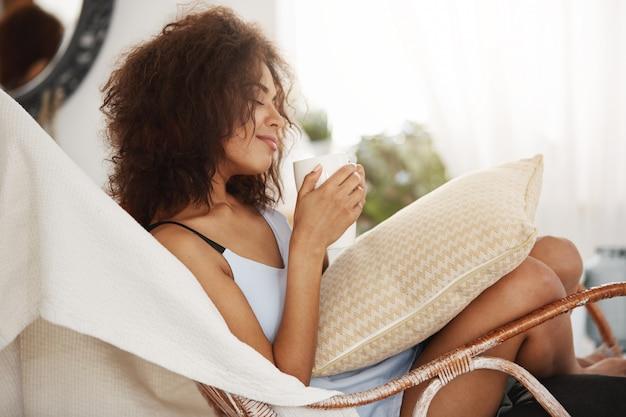Schöne afrikanische frau in nachtwäsche, die mit geschlossenen augen lächelt, die tasse, die im stuhl zu hause sitzt.