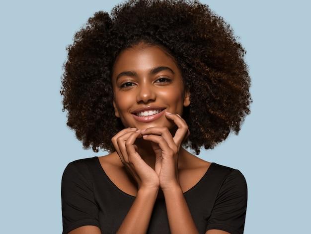 Schöne afrikanische frau schwarzes t-shirt porträt afro-haarschnitt, der ihr gesicht berührt farbhintergrund blau