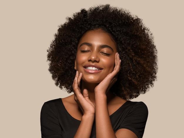 Schöne afrikanische frau schwarzes t-shirt porträt afro-haarschnitt, der ihr gesicht berührt farbhintergrund braun