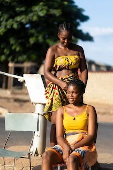 Schöne afrikanische frauen, die sich gegenseitig haare machen