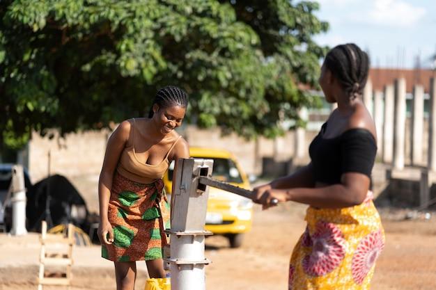 Schöne afrikanische frauen, die spaß beim wasserholen haben